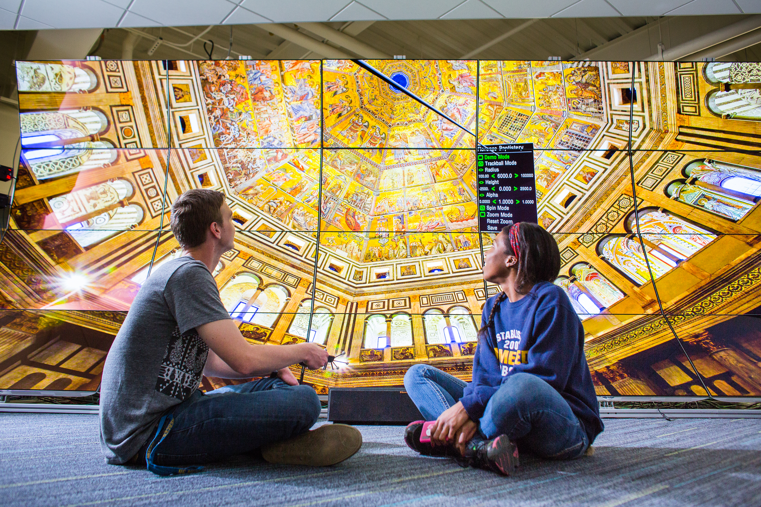 Students sitting in front of the WAVE Lab, where a large image of an ornate church ceiling is shown