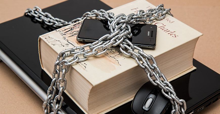 Black Phone on top of a book and a laptop, all 3 wrapped in heavy chains to symbolize keeping devices secure.